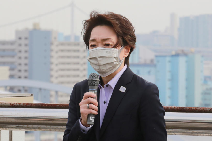 a person wearing a suit and tie who is looking at the cell phone: Seiko Hashimoto, President of the Tokyo 2020 Organizing Committee of the Olympic and Paralympic Games, speaks during her visits at Tsukiji Depot, Tokyo